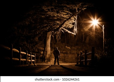 Night stalker concept. Man standing on wood bridge under street light in dark night