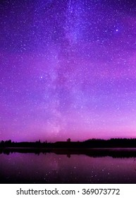 Night starry sky over a small lake.