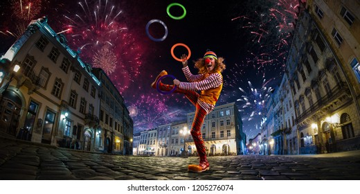 Night street circus performance whit clown, juggler. Festival city background. fireworks and Celebration atmosphere.