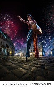 Night street circus performance whit clown. Festival city background. fireworks and Celebration atmosphere.