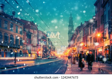 Night street decorated with Christmas holiday lights in Parma, Emilia-Romagna, Italy. Old architecture and landmark in Parma