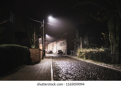Night street lit by flashlights