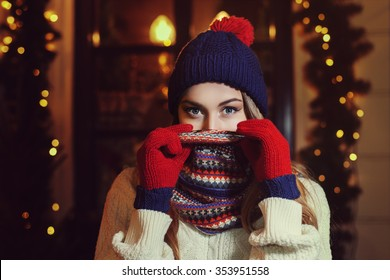 Night street portrait of young beautiful woman in classic stylish warm winter knitted clothes with scarf covering her face. Model looking at camera, Festive garland lights. Close up.