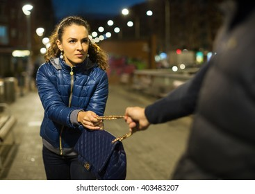 Night street robbery scene: man taking away woman bag