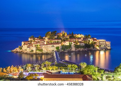 Night Sveti Stefan view with lights in windows, small islet and hotel resort in Montenegro, southeast of Budva. Balkans, Adriatic sea, Europe. Travel destinations background.