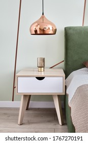 Night table near sleeping bed with modern metal bedroom lamp