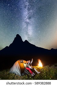 Night tent camping. Tourist pair - girl and guy sitting near tent and campfire and enjoying incredibly beautiful starry sky, Milky way in the background silhouette of the mountains. Low light