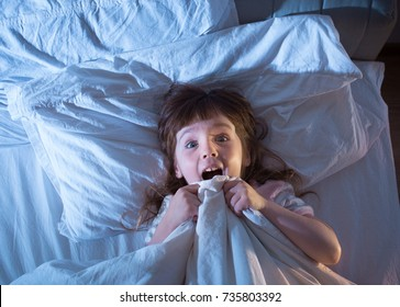 Night terrors of the child. Fear of the dark. The baby on the bed at night. An empty space to insert text.