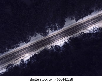 Night time aerial top down view of a snowy road surrounded pine tree forest in winter season.