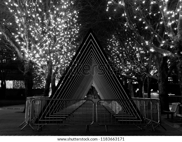 Night time black and white photo featuring lights in the trees and series of triangular metal arches.