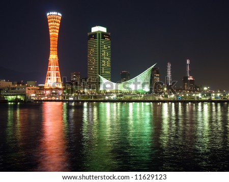 Night time cityscape view of Kobe port area with reflections on the harbour in the foreground
