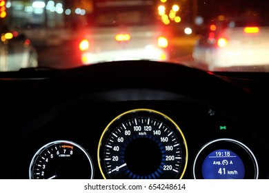 Night time close up steering wheel of car dashboard, modern light car mileage on the road between the traffic lights at night