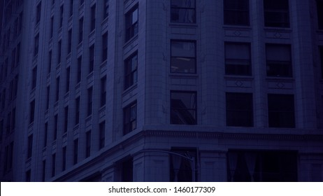Night time establishing shot of generic typical urban city apartment or office building at night time under blue tint moon light.