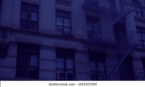 Night time exterior establishing shot outside a typical generic urban city style apartment building. Blue moon light effect. Setting for college dorm loft flat rented home
