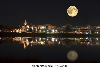 Night time in Fredericton New Brunswick with full moon and lights reflecting off the water of the Saint John River, Canada