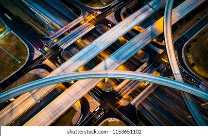 Night time illumination aerial drone view above Highways interchange aerial drone view lights and cars headlights and brake lights city urban transportation highways bridges connecting our city