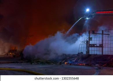 Night time inferno at a large industrial warehouse with fire truck ladder pouring water on flames