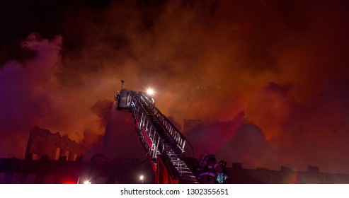 Night time inferno at a large industrial warehouse with unrecognizable firefighters fighting the flames