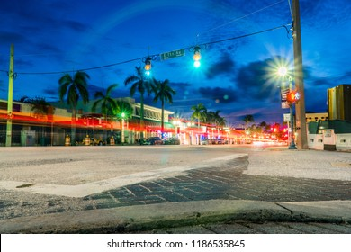 Night time long exposure of busy intersection in downtown Delray Beach Florida. Light trail from car vehicle traffic tail lights pass through green light and crosswalk countdown signal