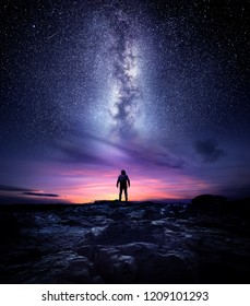 Night time long exposure landscape photography. A man standing in a high place looking up in wonder to the Milky Way galaxy, photo composite.