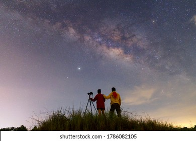 Night time long exposure landscape photography.the milky way,A couple standing in a high place looking up in wonder to the Milky Way galaxy, photo composite.