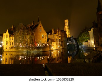 Night time shot of the Bruges / Brugge canals with belfry in the background and reflections in the water.