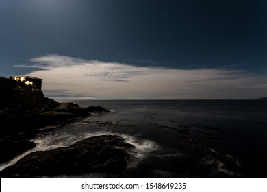 Night time view of a cliffside ocean view with a starry night sky and cirrus cloud and a cruise ship in the distance.