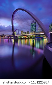 a night time view of elizabeth quay bridge with its reflection and city of perth australian and purple sky as background