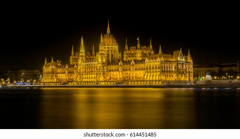 Night time view of the Hungarian Parliament building situated on the Pest side of the River Danube in Budapest, with light trails from passing boats visible in the foreground.