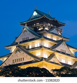 Night time view of the main tower of Osaka Castle lit up on the hillside with trees of the castle grounds around the base of the castle