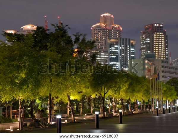 Night time view of Osaka skyline in the background with trees of a park and walkway in the foreground in the evening