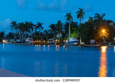 Night time view of shoreline river in tropical location as dark clouds and storm come off ocean. Boats raised above sea level for protection from storm surge and rising waters