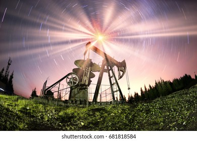 Night tour of the oil fields in the Ukrainian mountains of the Carpathians. The classic oil industry against the starry sky and the Milky Way in space symbolizes the energy of the universe