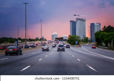 Night traffic. Cars on highway road at sunset evening in typical busy american city. Beautiful amazing night urban view with red, yellow and blue sky clouds. Sundown in downtown.
