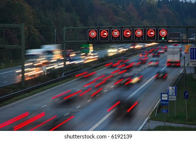 night traffic on autobahn with speed limit sign, motion blur