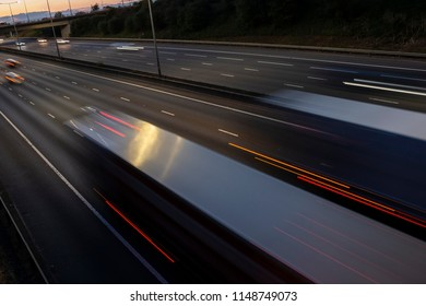 Night traffic on British motorway with cars and lorries blured in motion.