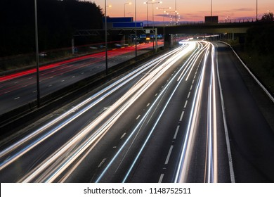 Night traffic on the British motorway. Red and white light trails created due to long exposure.