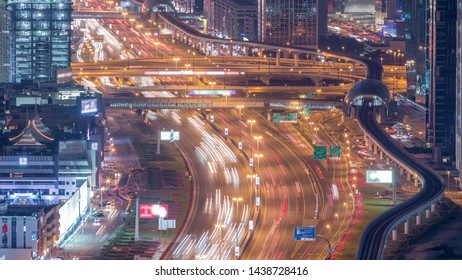 Night traffic on a busy intersection on Sheikh Zayed road highway aerial timelapse. View from rooftop with skyscrapers