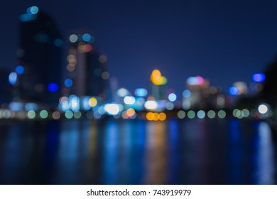 Night twilight blurred bokeh city downtown water front, abstract background