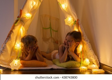 The night. Two little sisters indulge in the tent. Houses, before going to bed, bedside lamp