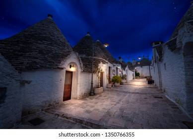 Night view of Alberobello's famous Trulli, the characteristic cone-roofed white houses of the Itria Valley, Apulia, Southern Italy. ALBEROBELLO, PUGLIA, ITALY