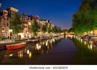 Night view of Amterdam cityscape with canal, bridge boats and medieval houses in the evening twilight illuminated. Amsterdam, Netherlands