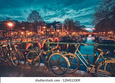 Night view of Amterdam cityscape with canal, bridge with bicycles and medieval houses in the evening twilight illuminated. Amsterdam, Netherlands