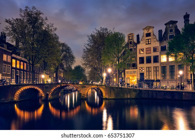 Night view of Amterdam cityscape with canal, bridge and medieval houses in the evening twilight illuminated. Amsterdam, Netherlands