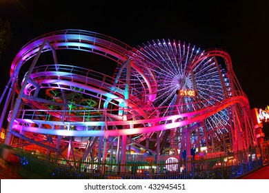 The night view of a amusement park with ferris wheel and roller coaster.  Photoed in Yokomaha, Japan.