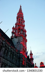 Night view of the ancient Town Hall illuminated in red at the Grand Place in Brussels, Belgium.