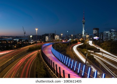 Night view of Auckland City from Hopetoun Street bridge with the motorway junction complex and pink bike path in the foreground. Auckland, New Zealand.