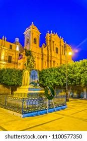 Night view of the basilica Minore di San Nicolò and the monumento ai caduti della grande guerra in Noto, Sicily, Italy