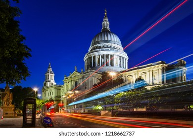 Night view of the beautiful facade of St Paul's Cathedral in the City of London, London, England, with the iconic red bus passing by. The dome of the church is one of the largest in the world