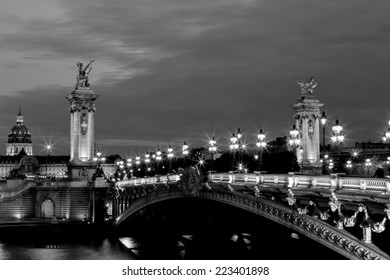 NIght view in black and white on the famous landmark Alexander iii bridge in Paris, capital of France, with beautiful characteristic street lights lighting the bridge and the dome of les invalides